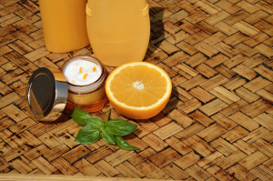 Orange face cream with half of orange and bottles of lotion and shower gel in background on wooden surface